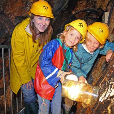 Kinder im Bergwerk bestaunen einen Bohrkern im Stollen.