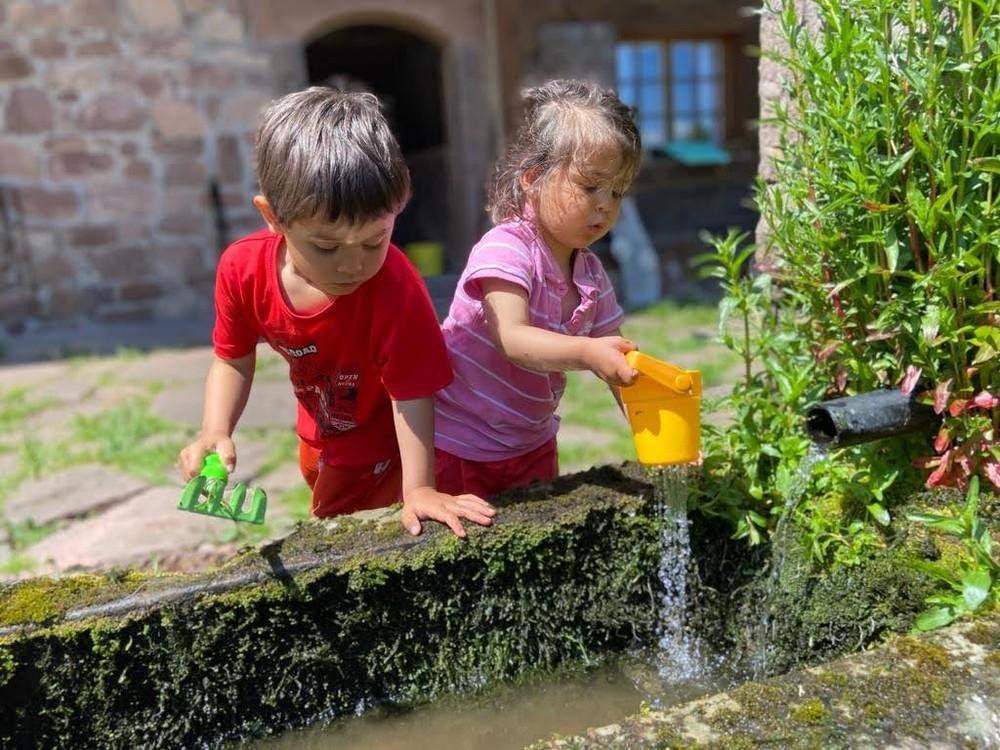 Kinder spielen an der Quelle