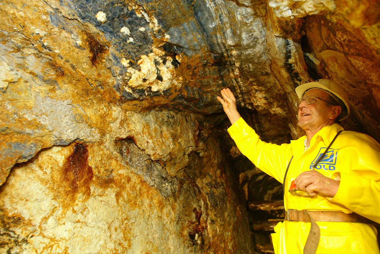 """Bergwerksführer Georg Allgaier zeigt verschiedene Mineralien bei einem Erzgang in der Grube """"Segen Gottes""""."""