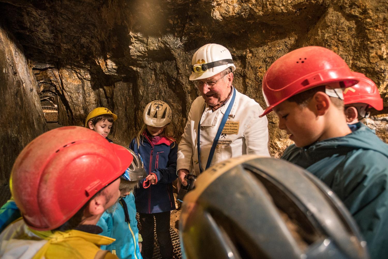 """Bergwerksführer Georg Allgaier ist mit Kindern im Besucherbergwerk """"Segen Gottes""""."""