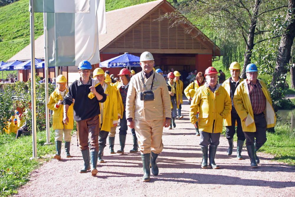"""Der Bergwerksführer begleitet seine Gruppe über den Steinpfad zum Stolleneingang der Grube """"Segen Gottes""""."""