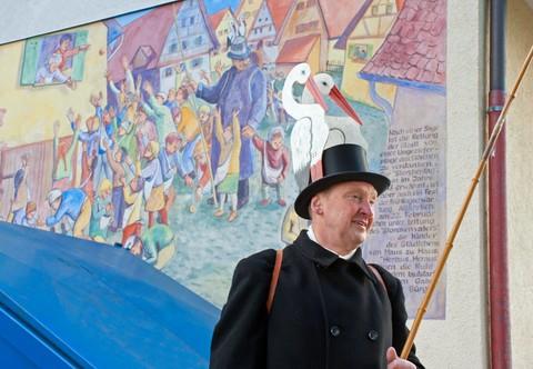 Der Storchenvater steht vor der Wandmalerei mit dem Storchentag